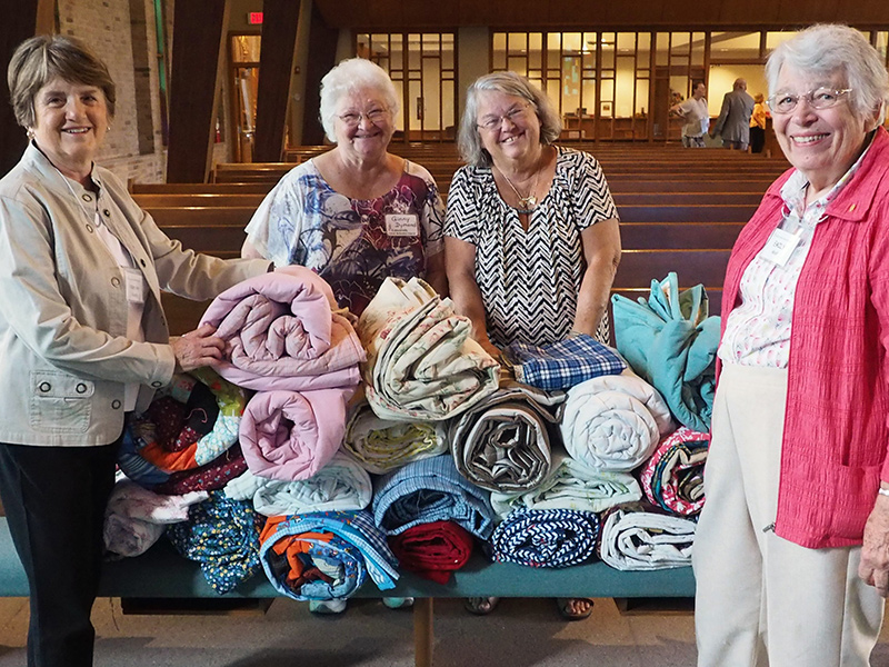 Four women standing in front of quilts to be donated